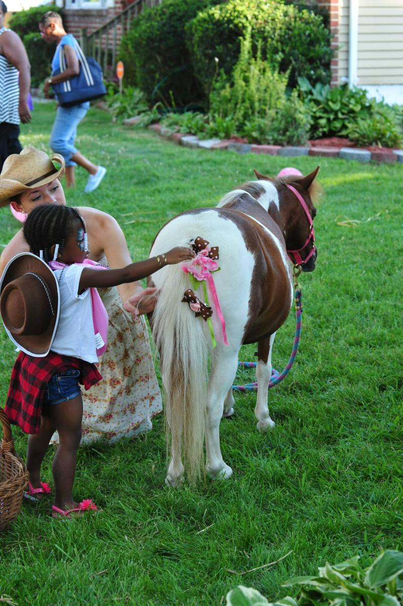 Little cowgirl pinning bows on Pocohantas at her birthday party