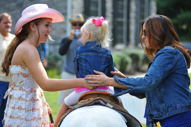 small pony rider being secured in saddle by pony walker and by her mother