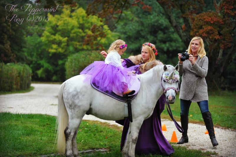 Beautiful fairy rides an elegant unicorn while mom takes a picture