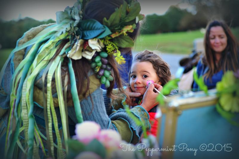 Miss Angela painting a pony on a cheek of a child at a Fairy Unicorn party