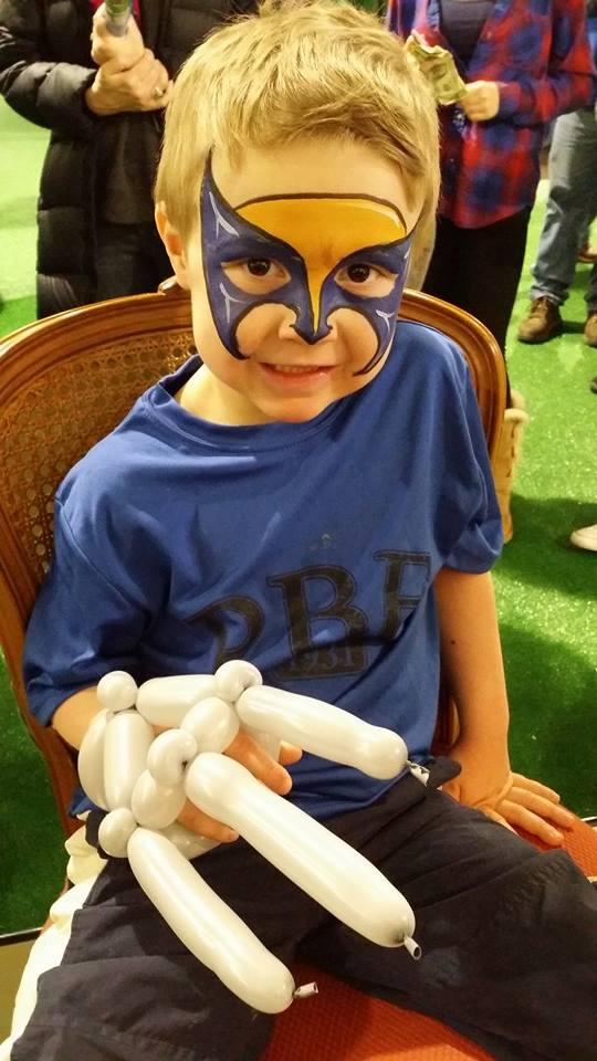 little boy with wolverine face painting and claws made from balloons